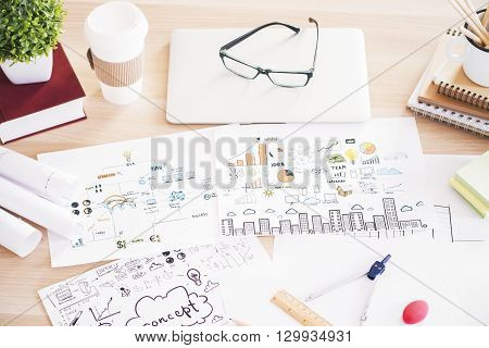 Closeup of wooden table with business sketches office tools and other items