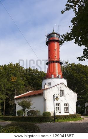 Red and white lighthouse on a sunny day with blue sky.