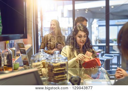 Young Brunette Woman Making Payment At A Till