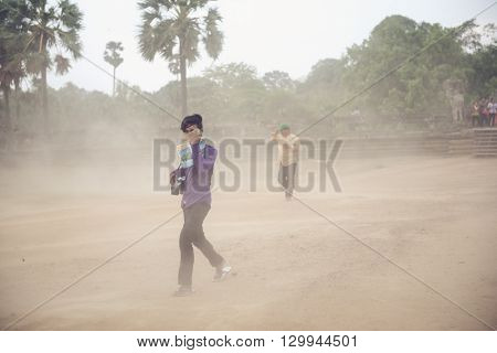 Siem Reap, Cambodia - MAY 04, 2016: Tourists from China caught in a sandstorm