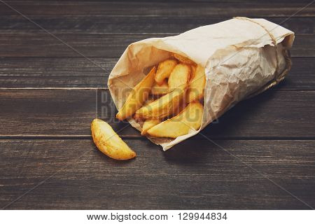Tasty potato wedges wrapped into brown kraft wrapping paper. Fast food take away. Fried potatoes at rustic wooden boards background. Potatoes at wood. Fried chips, potato slices. Top view, soft tone