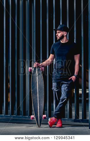 Full body portrait of bearded stylish man with longboard. Young man with a beard wearing a stylish black clothes. Stylish red sneakers and fashionable cap. Handsome guy posing on metal fence.