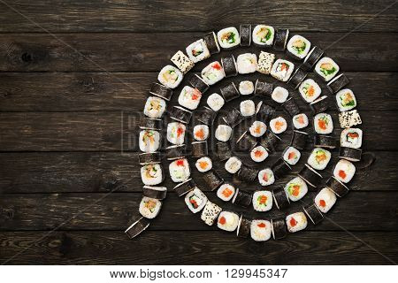 Japanese food restaurant, sushi maki roll plate or platter set. Maki Sushi rolls at rustic wood background. Top view, flat lay. Big party sushi set, copyspace