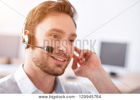 Best service for you. Portrait of positive handsome smiling man using headset with micro and talking with client while working in the call center