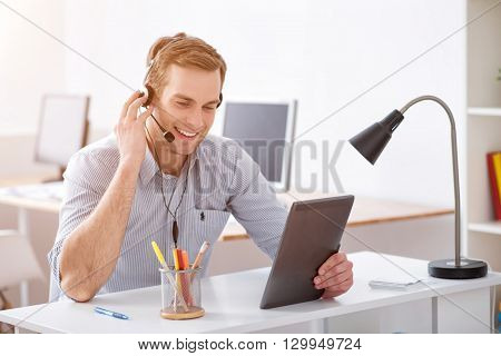 In a good mood. Cheerful delighted smiling man sitting at the table and talking by the help of headset with micro while holding tablet