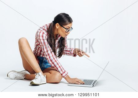 Beautiful geek woman pointing to the laptop in studio on white