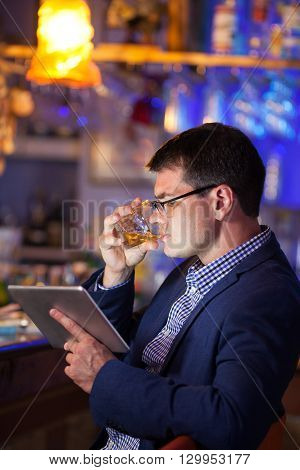 Businessman wearing glasses seated at the bar counter enjoying a drink at a club while reading on his tablet computer