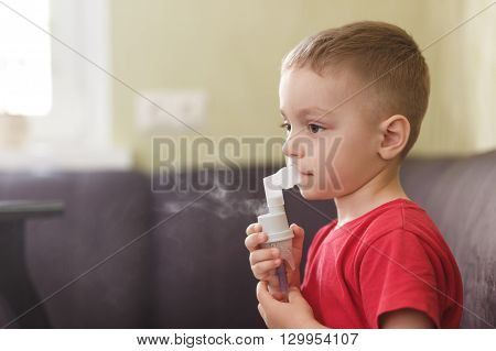 Small boy does therapeutic inhalation using a nebulizer