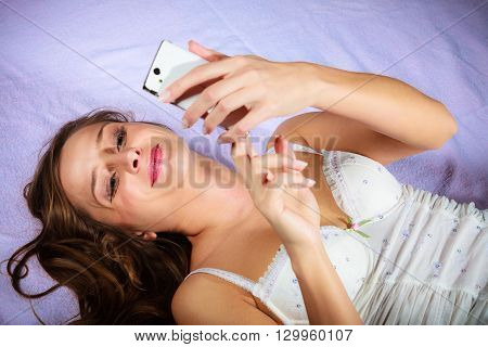 Texting and calling concept. Beauty young long haired woman lying on bad holding smartphone and texting.
