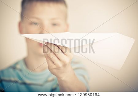 Out Of Focus Child Holding Paper Airplane