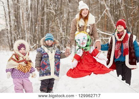 Four children of different age stand around stuffed dummy of Maslenitsa, sitting on snowbank in winter park.
