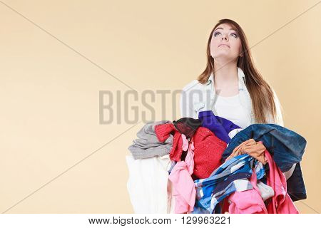 Young woman carrying stack pile of dirty laundry clothes. Girl cleaning tidying in studio.