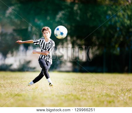 TURIN, ITALY - MAY 15, 2016: Caucasian boy kicks the ball during a football match. The kid dresses the black and white uniform of Juventus, the major italian football team.
