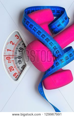 healthy lifestyle fitness weight control concept. Closeup pink dumbbells with blue measuring tape on white scales