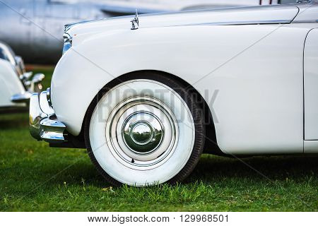 Close-up of the front part of the old white retro car. Fender and the front wheel of the car. White vintage car. Side view. Selective focus.
