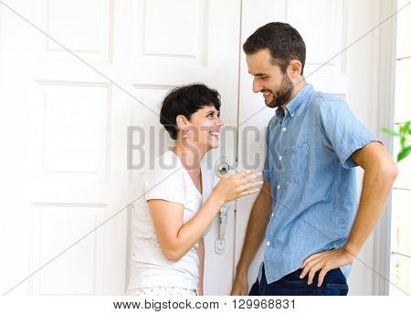 A man jokes with a girl. She laughs. Outdoor photo.