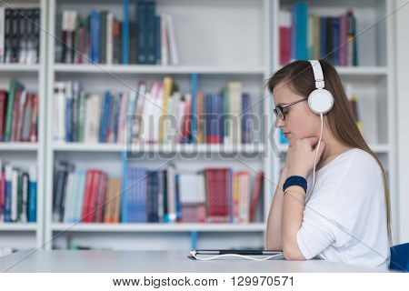 female student study in library using tablet and searching internet while  Listening music and lessons on white headphones