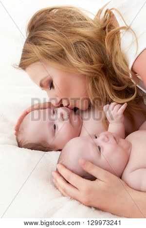 Mother kissing her daughters - newborn twin babies. Motherhood, maternity love concept.