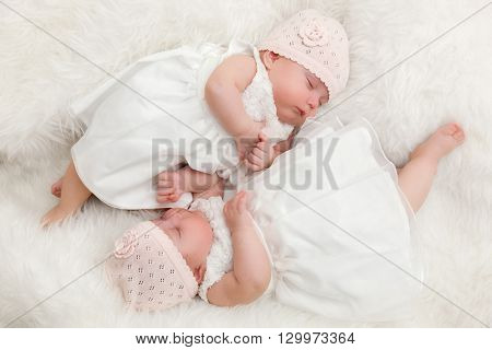Cute twin sisters, newborn babies lying together. Wearing elegant white dresses