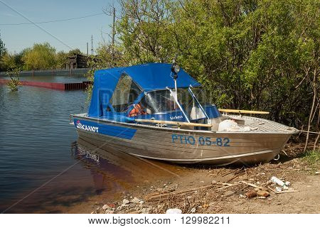 Tyumen, Russia - May 16, 2016: The spread river Tura has flooded the house on Tomskaya Street. The boat of rescuers is moored to a dam