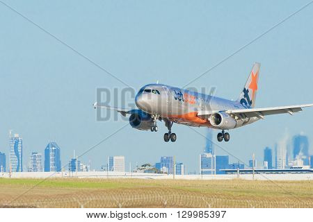 Melbourne, Australia - May 6, 2016: Close-up view of a Jetstar passenger airplane landing at Melbourne Airport, with CBD skyline in the background