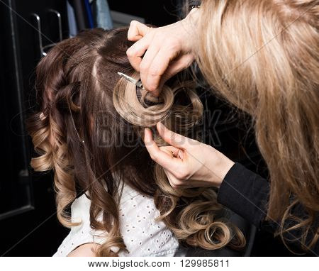 Master stylist makes the bride wedding styling. beautiful satisfied client in professional hairdressing salon.