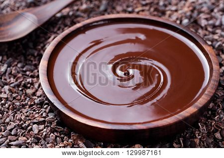 Bowl of melted chocolate and wooden spoon on a crushed raw cocoa beans, nibs background. Copy space.
