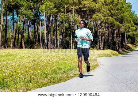 Action shot of young african woman with braids jogging on tar road in green field.
