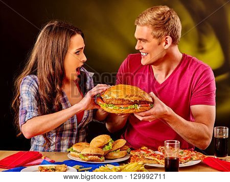 Young couple male and woman eating hamburgers . Fastfood concept.  Very big fast food hamburgers.