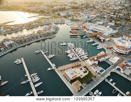 Aerial view of the beautiful Marina in Limassol city in Cyprus the beach boats piers villas and commercial area. A very modern high end and newly developed space where yachts are moored and it's perfect for a waterfront promenade.