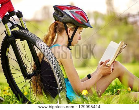 Bikes cycling girl. Girl rides bicycle. Girl in cycling read book on rest near bicycle. Cycling is good for health. Cyclist back view.