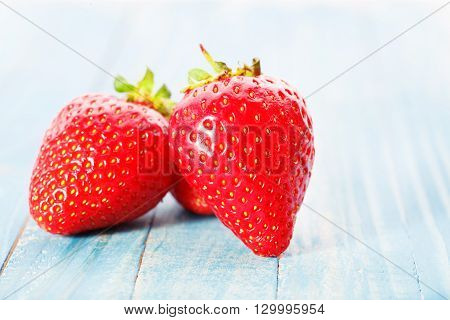 Two strawberries on a blue wooden table