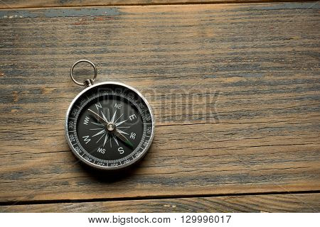 compass on the brown wooden table background top view