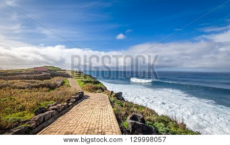 Walking path on the edge of the ocean in Calhau das Achadas beautiful bay. Madeira island, Portugal.