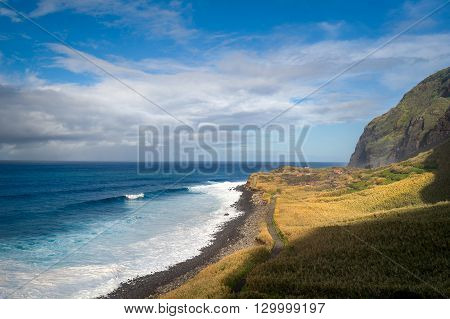 Wild bay Calhau das Achadas aka The Bay of Discoverers landscape with calm ocean waves, fields lit by sun and steep mountains. Madeira island, Portugal.