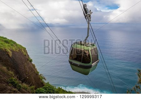 Steep cable car way from the mountain cliff to the ocean bay. Calhau das Achadas, Madeira island, Portugal.