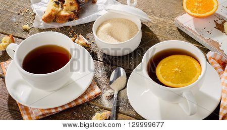 Two Cups Of Tea With Cake And Orange