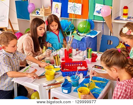 Children with teacher woman painting on paper at table  in  kindergarten . Children learn painting in start school.