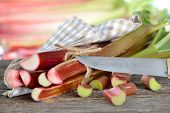 Fresh rhubarb on a wooden table with an old chef's knife, in the background other rhubarb stalks in soft focus poster