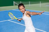 Asian tennis player woman playing hitting forehand in white dress outfit on blue hard court outdoor in summer holding racket. Female athlete determination and concentration concept. poster