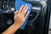 Hand with microfiber cloth cleaning Interior modern car. poster