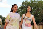 Rustenburg Marathon Club Rainbow Run - NOVEMBER 25: Two Chearful running young Indian girls covered with powder paint at colour run on November 25 2015 Rustenburg South Africa. poster