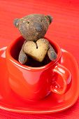 teddy bear handmade and cookie in the form of heart in a cup on a red background poster