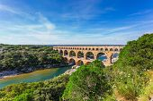 Three-tiered aqueduct Pont du Gard was built in Roman times on the river Gardon. Around the bridge is magnificent natural park. Provence, spring sunny day poster