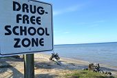 sign saying drug-free school zone at the beach poster