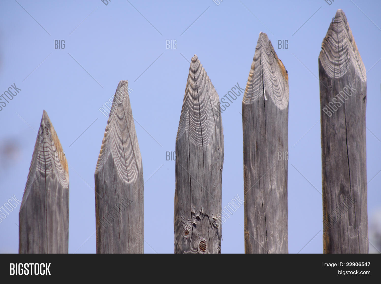 Wooden Spike Fence With Blue Sky Background