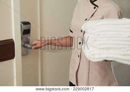 Maid Opening Door Of Hotel Room To Change Sheets And Towels
