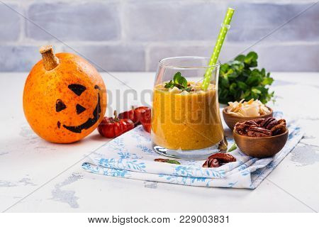 Pumpkin Smoothie With Coconut Chips, Pecan Nuts, Cinnamon And Mint. Halloween Or Thanksgiving Day De