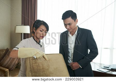 Maid Showing Spot On Sofa Pillow To Manager