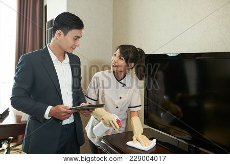 Hotel Manager Asking Maid To Wipe Furniture In Room